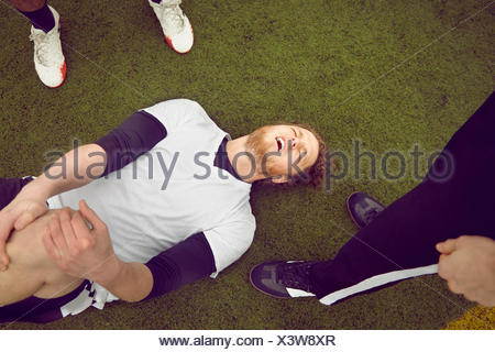 Injured male soccer player on soccer pitch - Stock Photo