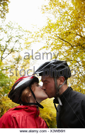 Couple wearing cycle helmets kissing - Stock Photo