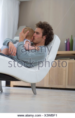 Father kisses baby, sits in chair - Stock Photo
