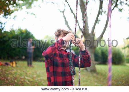 Trainee teenage male tree surgeon preparing climbing ropes - Stock Photo