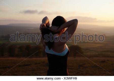 Runner tying her hair in rural landscape - Stock Photo