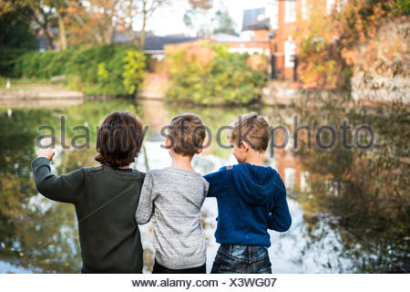Three young boys, standing beside lake, rear view - Stock Photo