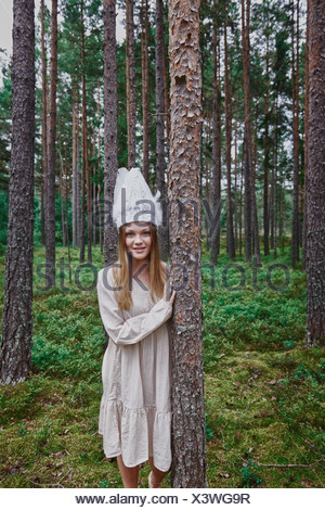Teenage girl wearing white hat in forest - Stock Photo