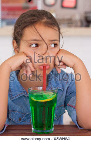Grumpy girl drinking mocktail through a straw - Stock Photo