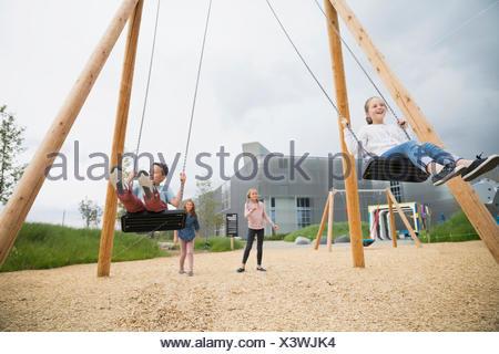 Girls swinging at playground - Stock Photo