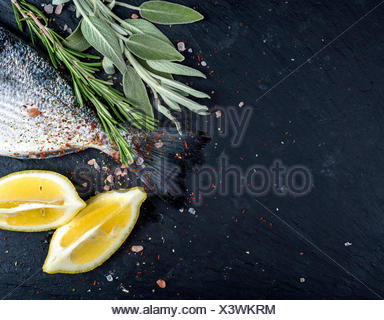 Tail of fresh raw Dorado or sea bream fish on black slate stone board with spices, herbs, lemon and salt. Top view, copy space - Stock Photo