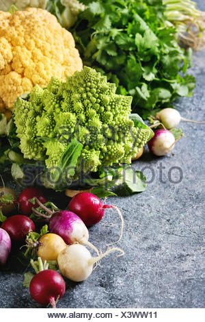 Variety of fresh raw organic colorful cauliflower, cabbage romanesco and radish with bundle of coriander over dark texture background. Close up with s - Stock Photo