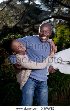 A man playfully carries his wife, Illovo Family, Johannesburg, South Africa. - Stock Photo