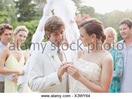 Bride putting ring on groom's finger - Stock Photo