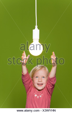 Little girl reaching for hanging light bulb - Stock Photo