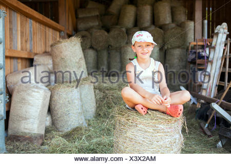 Little girl sitting on hay bale in stable - Stock Photo