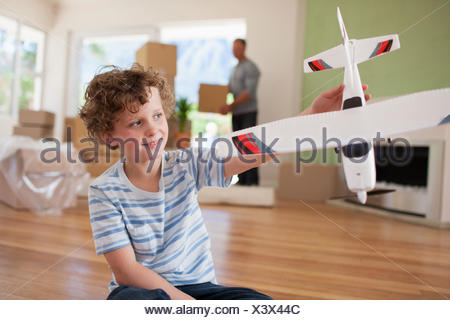 Boy playing with airplane in new home - Stock Photo