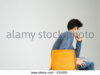 Young man sitting on chair, holding chin - Stock Photo