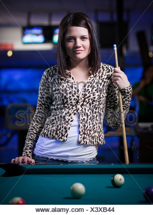 USA, Utah, American Fork, young woman standing behind pool table - Stock Photo