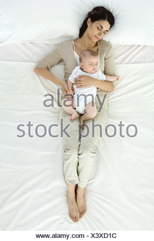 Mother and baby napping together on bed, overhead view - Stock Photo