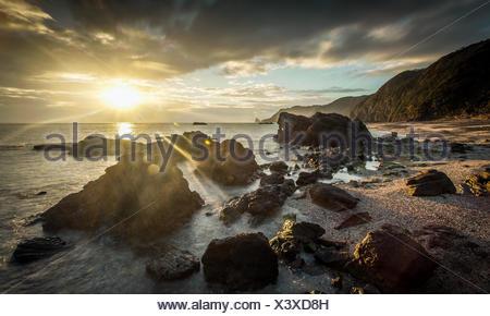 Japan, Okinawa, Sunrise over ocean and rocks - Stock Photo