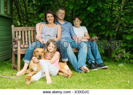 Portrait of family with two children sitting on garden bench with dog - Stock Photo