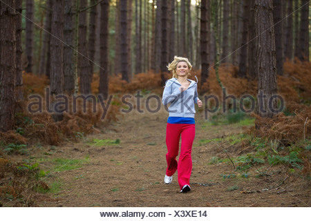 Smiling woman running in woods - Stock Photo