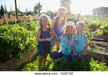 Portrait smiling grandmother and grandchildren sunny community garden - Stock Photo