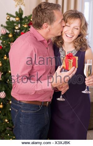 Couple kissing near Christmas tree - Stock Photo