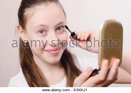 Teen girl having a fun painted cosmetics. - Stock Photo