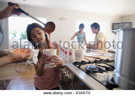Mother and daughter cooking soup, pouring into container in kitchen - Stock Photo