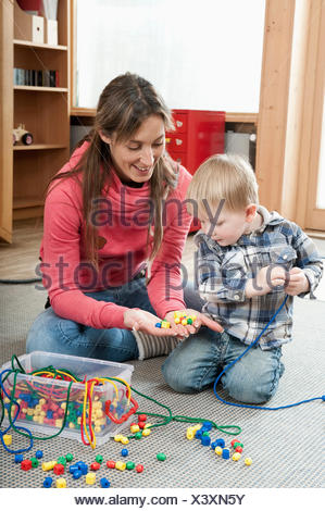 Female educator offering little boy wooden perls for making a necklace - Stock Photo