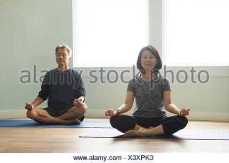 Mature couple sitting cross legged on yoga mat meditating eyes closed - Stock Photo