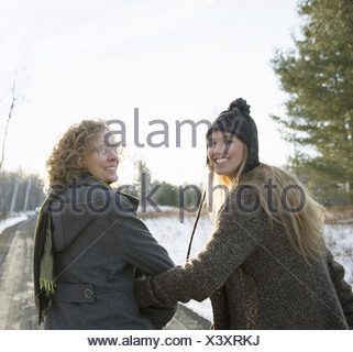 A mother and daughter arm in arm walking along a path and looking over their shoulders - Stock Photo