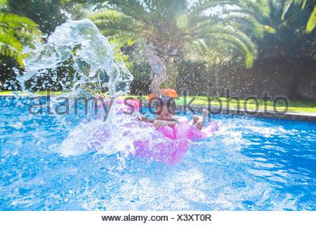 Girl and boy splashing around in garden swimming pool - Stock Photo