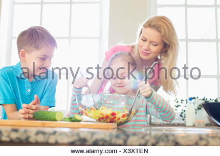 Family looking at girl mixing salad in kitchen - Stock Photo