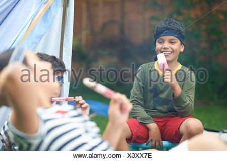 Girl and two brothers eating ice lollies in garden - Stock Photo