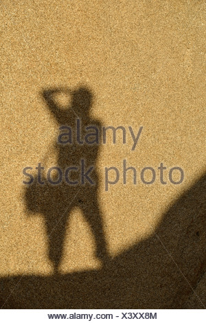 Shadow of a photographer on a monzogranite rock formation, Hidden Valley, Joshua Tree National Park, Mojave Desert, California - Stock Photo