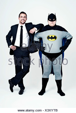 Athletic man wearing a suit beside a fat man dressed as a superhero, Batman - Stock Photo