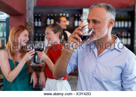 Man drinking red wine while two friends toasting the glasses in background - Stock Photo