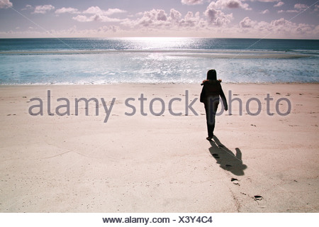 girl standing on a deserted beach - Stock Photo