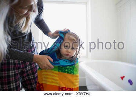 Mother drying grumpy daughter off with towel bathroom - Stock Photo