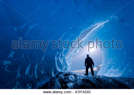 COMPOSITE: View from inside an ice cave of an iceberg frozen in Mendenhall Lake as an ice climber stands at the entrance, Alaska - Stock Photo
