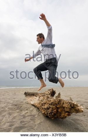 Businessman jumping over a tree trunk on a beach - Stock Photo