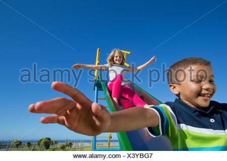 Smiling children sliding on slide - Stock Photo