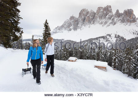 two models are walking with their sleddings along a winter path with the Geisler in the background, Villnoss, South Tyrol, Trentino Alto Adige, Italy, Europe - Stock Photo