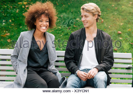 Sweden, Vastra Gotaland, Young smiling couple sitting on bench in park - Stock Photo