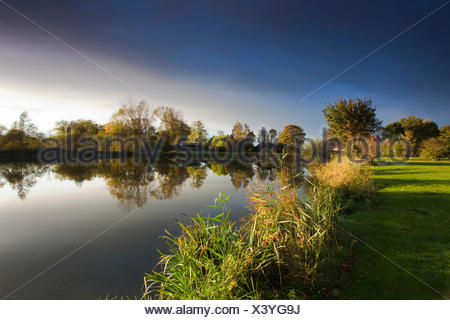 sun shining on a lake shore through a hole in a cloud cover, Germany, Lower Saxony, Vogtlaendische Schweiz, Dorum-Neufeld - Stock Photo