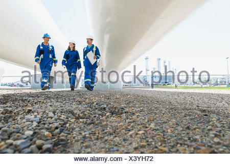 Workers walking below tanks at gas plant - Stock Photo