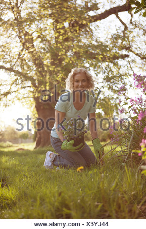 A mature woman planting flowers in a garden - Stock Photo