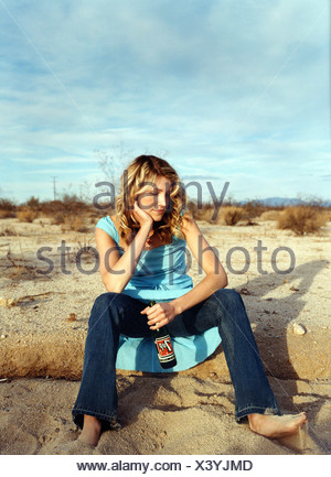 Female curled blonde hair wearing turquoise blue sundress dark blue jeans sitting on sand elbows on knees sifting through sand - Stock Photo