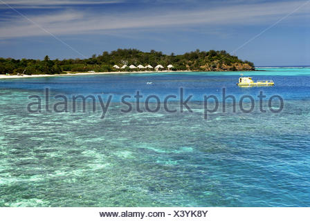 Fiji, Mamanuca Islands, Mana Island, Yellow Semi Submersible Vessel In Lagoon, Bures Line The Shore, View From Ocean. - Stock Photo
