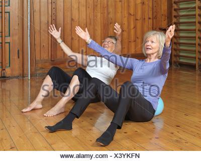 Women practicing yoga together in studio - Stock Photo