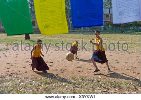 Young monks playing football, Tibetan refugee settlement in Bylakuppe, Mysore District, Karnataka, South India, India, Asia - Stock Photo