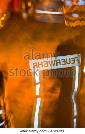backside of a firefighter with flames - Stock Photo